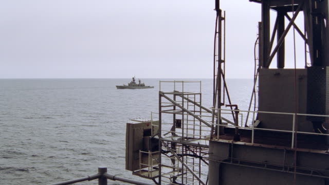 a metal sentry overlooks a battleship floating in a calm bay. - warship stock videos & royalty-free footage