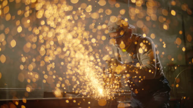 vídeos de stock, filmes e b-roll de slo mo ds metal sparks flying from the cutting tool - foundry
