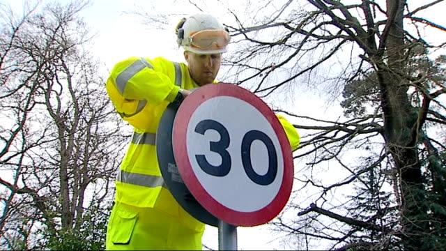 surrey county council replaces stolen signs with plastic ones; england: surrey: elstead: ext workman up ladder removing metal speed limit sign... - 道を譲る点の映像素材/bロール