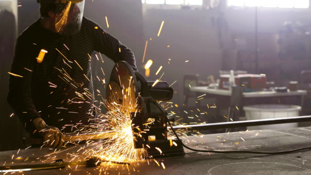 Metal worker cutting iron bar with circular saw in a workshop.