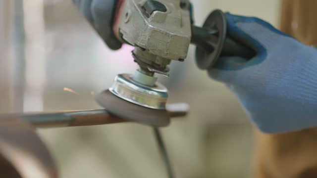 cu metal worker grinds rust off a metal pole with an angle grinder - metalwork stock videos & royalty-free footage