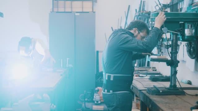 ドリルプレス (スローモーション) を使用した金属作業員 - アルゼンチン文化点の映像素材/bロール