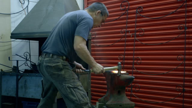 Metal worker witih hammer forging hot iron at anvil