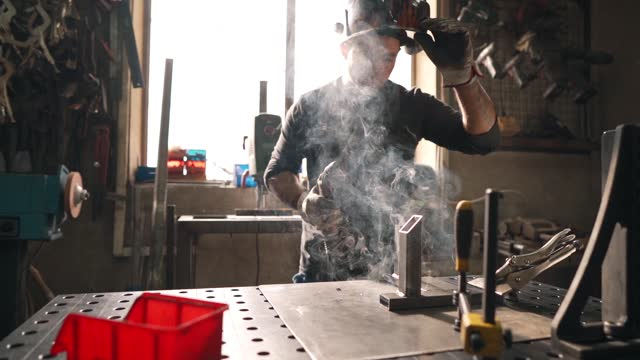 metal worker working on a metal frame at his workshop while using a welding torch - welding helmet stock videos & royalty-free footage