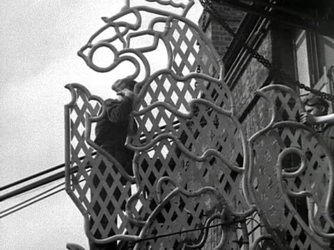 metal workers add the finishing touches to a hanging model of a lion that will be used to decorate the mall during the coronation celebrations. 1953. - insignier bildbanksvideor och videomaterial från bakom kulisserna