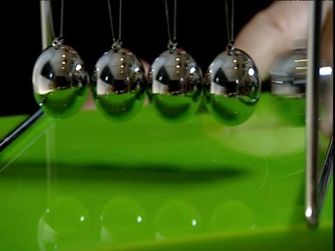 stockvideo's en b-roll-footage met metallic balls of newton's cradle collide back and forth - slinger van newton