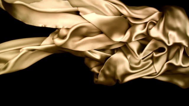 vidéos et rushes de metallic champagne gold silky fabric flowing and waving horizontally in super slow motion and close up, black background - champagne