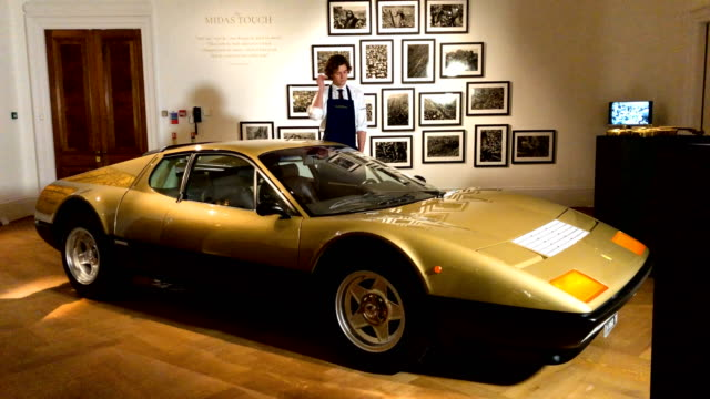 a metallic gold 1977 ferrari 512 bb sits on display during a media preview at sotheby's auction house for their 'midas touch' auction on october 12... - サザビーズ点の映像素材/bロール