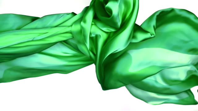 metallic green silky fabric flowing and waving horizontally in super slow motion and close up, white background - levitation stock-videos und b-roll-filmmaterial