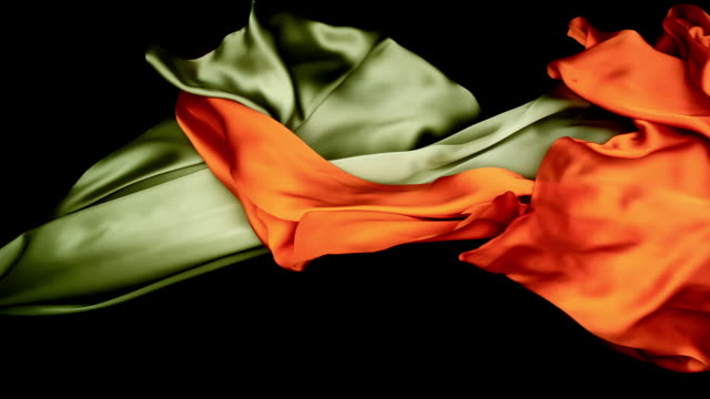 metallic silver and orange silky fabrics flowing and waving horizontally in super slow motion and close up, black background - orange stock videos & royalty-free footage
