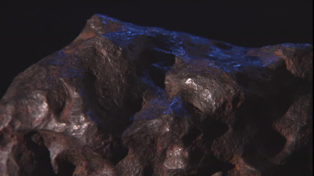 a meteorite on display begins rotating against a black background. - payson stock videos & royalty-free footage