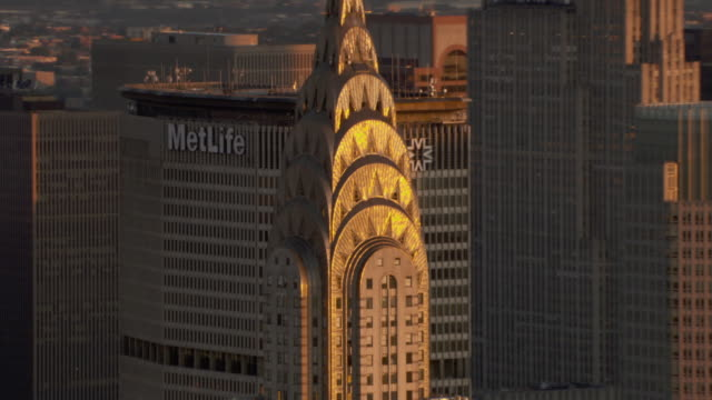 a metlife sign hangs on a skyscraper behind the chrysler building in manhattan. - metlife hochhaus stock-videos und b-roll-filmmaterial