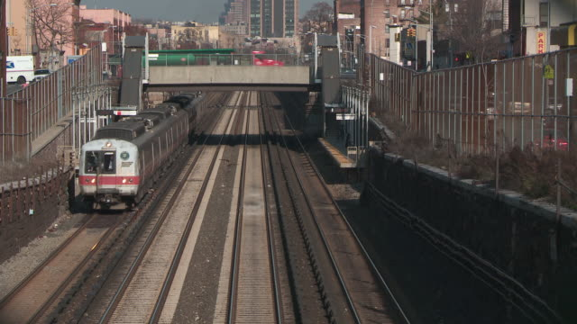 Metro north train passes through the bronx as cars pass on an overpass in the back during the day