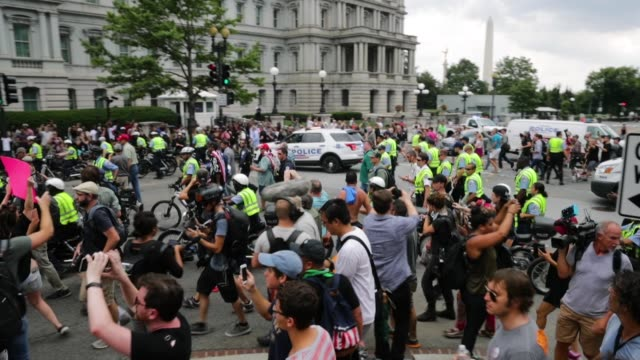 dc metro police form a protective phalanx around participants in the white supremacist unite the right rally to separate them from counter protesters... - racism stock videos & royalty-free footage