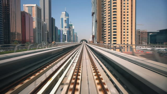 ws pov metro rail riding through cityscape / dubai, united arab emirates - zugperspektive stock-videos und b-roll-filmmaterial