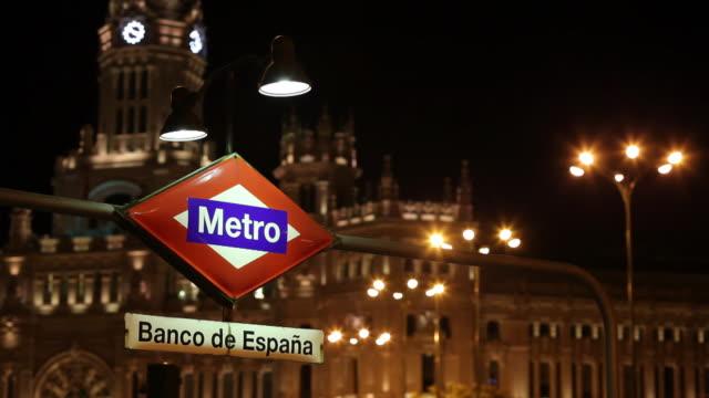 cu  metro sign with banco espanol de credito illuminated at night / madrid, spain - madrid stock videos & royalty-free footage
