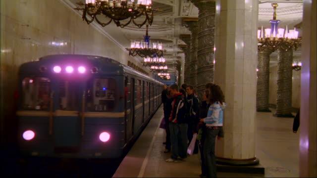 A metro train approaches the platform where passengers wait.