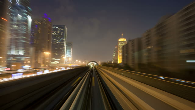 A Metro Transportation Railway train travels through lighted stations and tunnels along Sheikh Zayed Road.