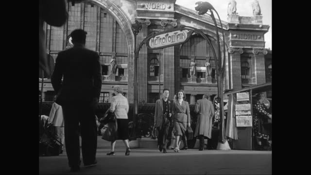 vídeos de stock, filmes e b-roll de ms metropolitain sign with pedestrian and cars moving on street in front of gare du nord / paris, france - 1950