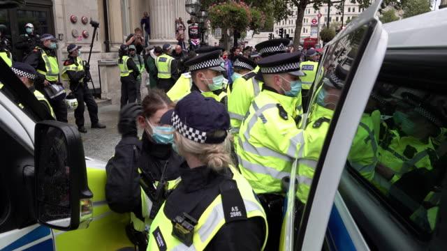 metropolitan police escort an arrested coronavirus conspiracy protestor into a police van following clashes at the anti-lockdown, anti-vaccination... - トラファルガー広場点の映像素材/bロール
