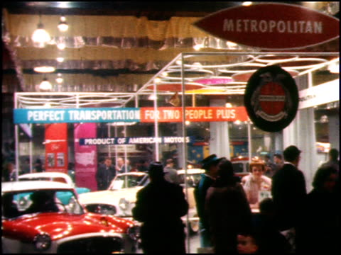 metropolitans on display at the 1959 chicago auto show / ms literature booth pretty woman hands out literature to attendees / ms attendees file by a... - 1959 stock videos & royalty-free footage