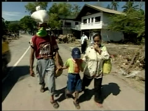 Tsunami survivors covering their faces towards along road Mother father and child covering faces towards CS Father clutching child's arms tightly BV...