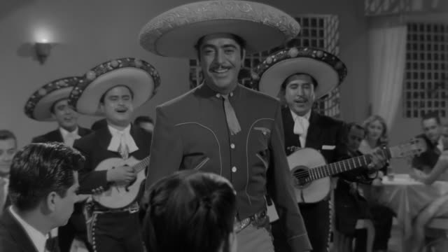 mexican actor and singer luis aguilar singing dressed as mariachi with three more men playing guitar walking around the club with elegant dressed... - mexican ethnicity stock videos & royalty-free footage