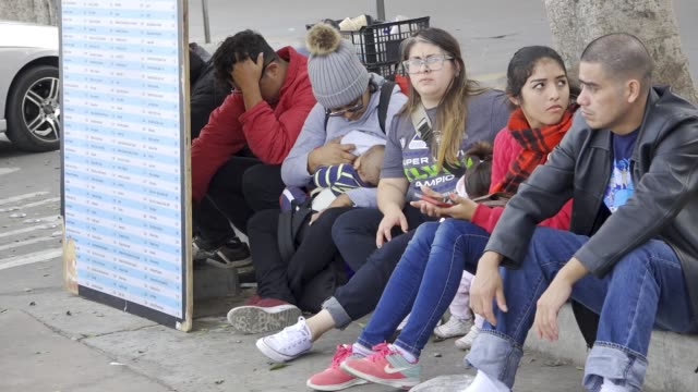 mexican central americans and africans wait at san ysidro port of entry for their waiting list number to be called to request asylum in the united... - baja california norte stock videos & royalty-free footage