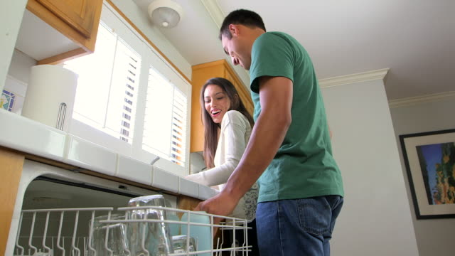 mexican couple doing the dishes together - dreiviertelansicht stock-videos und b-roll-filmmaterial