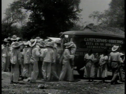 mexican crowd reaching for literature ws mexican peons around truck ext vs mexicans reading books cu communist book ms communist poster - 1934 stock-videos und b-roll-filmmaterial