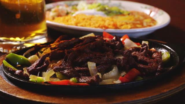 vídeos y material grabado en eventos de stock de cocina mexicana sizzling beef steak fajitas en un restaurante mexicano de lujo - preparación de alimentos