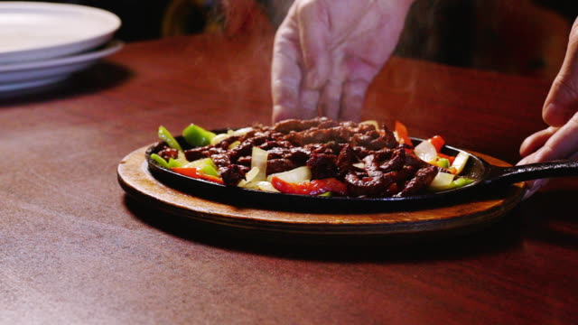 mexican cuisine sizzling beef steak fajitas in a fancy mexican restaurant - chopped food stock videos and b-roll footage