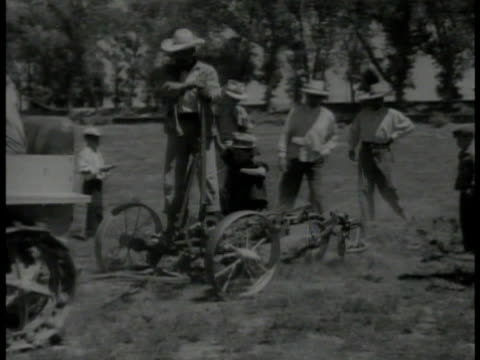 vídeos de stock e filmes b-roll de mexican farmers starting tractor ms farmer w/ boy on tractor pulled plow ms young adult students crowded around instructor vs students hoeing... - 1935