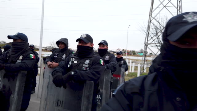 vídeos y material grabado en eventos de stock de mexican federal police keep guard around a hostel where migrants are staying while waiting to apply for asylum in to the united states on february... - convoy