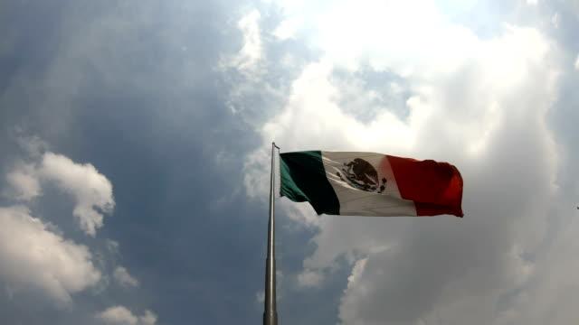vidéos et rushes de drapeau mexicain contre un ciel nuageux - mexico