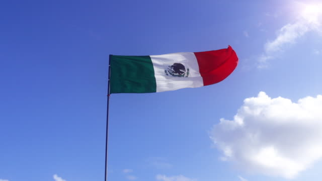 mexican flag blowing in the wind against blue sky with clouds - cancun stock videos & royalty-free footage