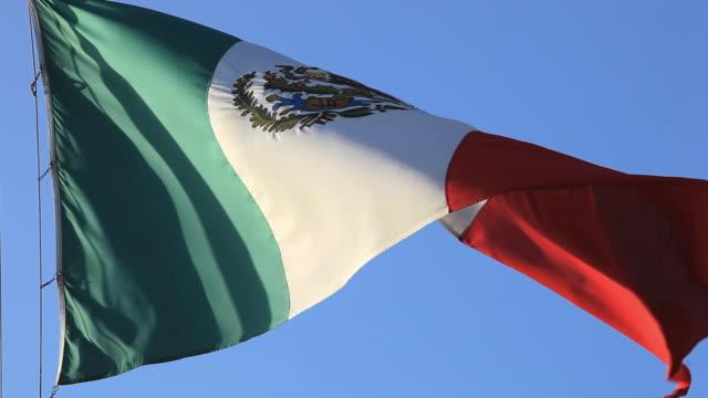 CU LA Mexican flag blowing in wind, Izamal, Yucatan, Mexico