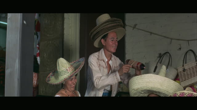 1967 ms mexican hat vendor smiling and playing traditional instrument - ギフトショップ点の映像素材/bロール
