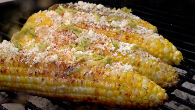 mexican lime street corn with cotija cheese and chili powder - mexican culture stock videos & royalty-free footage