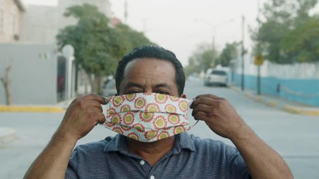 vídeos de stock, filmes e b-roll de homem mexicano na casa dos 50 anos colocando uma máscara n95 covid usada para achatar a curva e retardar a propagação na cidade de ciudad juárez, chihuahua no norte do méxico perto do muro internacional da fronteira eua/méxico - méxico