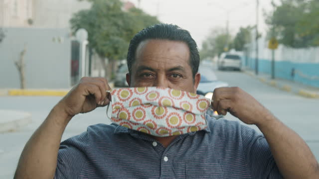 mexican man in his fifties taking off an n95 covid mask used to flatten the curve and slow the spread in the city of ciudad juárez, chihuahua in northern mexico near the us/mexico international border wall - international border stock videos & royalty-free footage