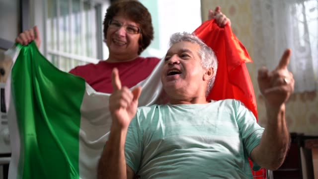 Mexican senior couple fan watching soccer game at home