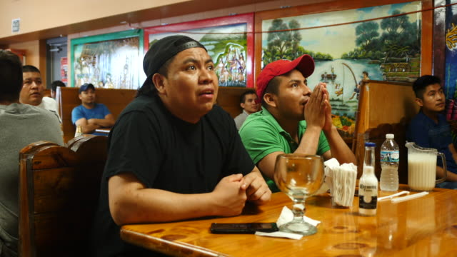 Mexican soccer fans watching the game on television at La Bonita Mexican restaurant in Bloomington Indiana react as Mexico plays Brazil during the...