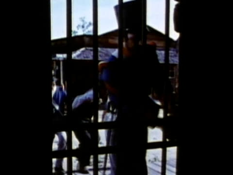 1963 reenactment ms mexican soldiers throwing american settler in jail cell / 1830s texas / audio - espansione verso l'ovest video stock e b–roll
