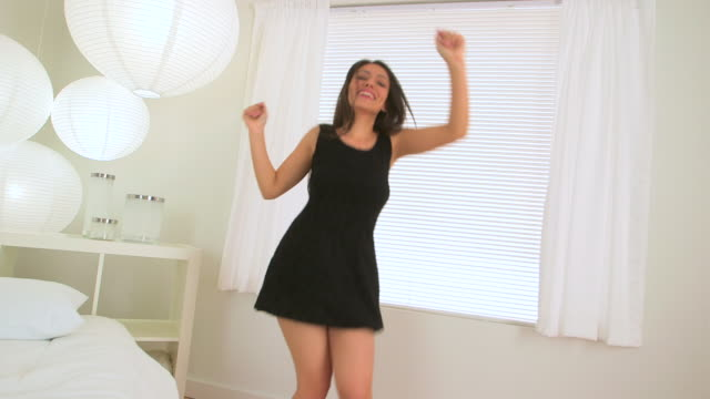 mexican woman dancing in black dress in bed room - dreiviertelansicht stock-videos und b-roll-filmmaterial