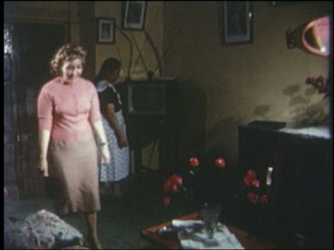 vídeos de stock e filmes b-roll de 1963 mexican woman turns on television in living room, large family enters + sits down - 1963