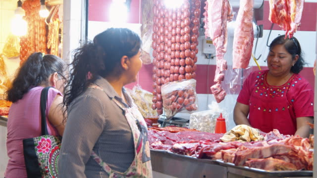 mexican women buying at butcher stall market at oaxaca mercado benito juarez, mexico - market stall stock videos & royalty-free footage