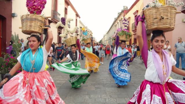 vídeos de stock e filmes b-roll de mexican women dancing dressed in traditional costume. they are named chinas and are performing a choreography with the colourful skirts. mexico tradition. calendas is a parade and celebration typical from oaxaca state - tradição
