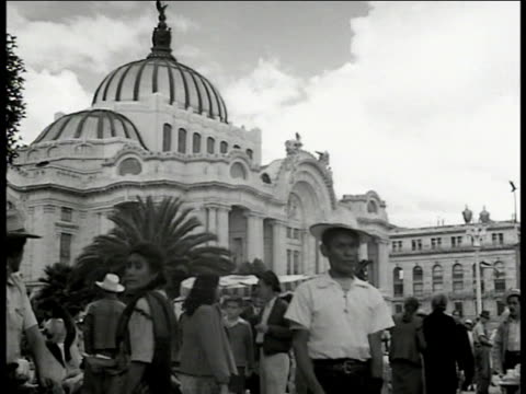mexicans buying newspaper from stand on street, presidential palace bg. pedestrians, church building. book store window. books in window about... - mexikanischer abstammung stock-videos und b-roll-filmmaterial