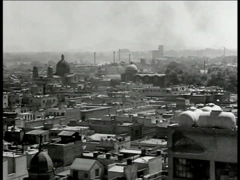 stockvideo's en b-roll-footage met cu 'mexico' illustrated poster ws mexico city ws la plaza de la constitucion building ws cattle on street trucks fg vs cars buildings mexicans riding... - 1946